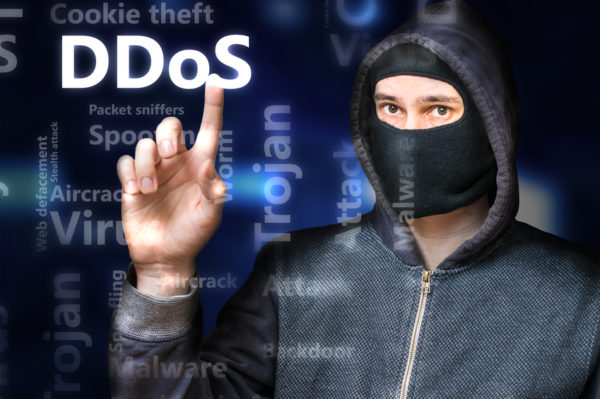 Masked anonymous hacker is pointing on DDoS Attack